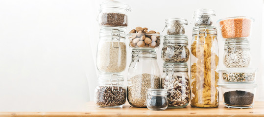 Banner with assortment of uncooked grains, cereals and pasta in glass jars on wooden table. Healthy cooking, clean eating, zero waste concept. Balanced dieting food. Copy space