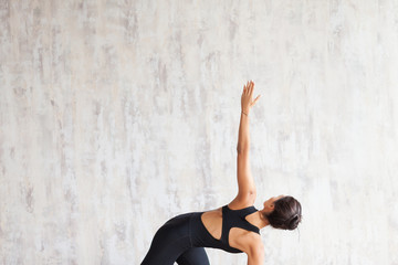 Slender asian yoga girl practicing yoga against concrete wall, stretching body. Girl standing in Trikonasana exercise, extended triangle pose, wearing black sportswear, yoga studio, no stress concept