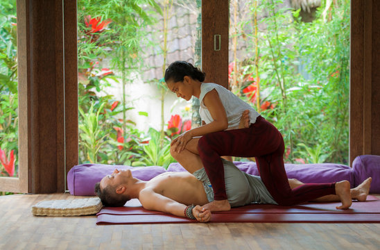 young beautiful and exotic Asian Indonesian therapist woman giving traditional Thai massage to man relaxed at tropical wellness spa in healthy natural lifestyle