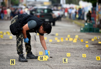 A forensic technician looks for bullet casings on the ground at a crime scene after a shootout in the municipality Tuzamapan