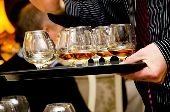Cognac glasses on a waiters tray