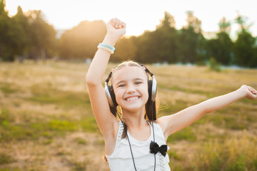 happy girl having fun on nature, active child with black and silver headphones listening music and dancing