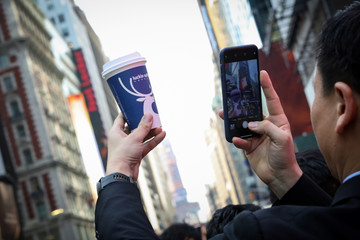 A company executive photographs a Luckin Coffee cup during the company's IPO at the Nasdaq Market site in New York
