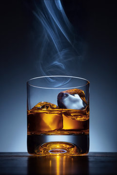 Whiskey glass with ice and cigar smoke over the top on wooden tale