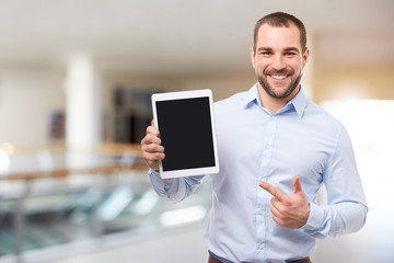 Happy businessman in blue shirt shows touch screen in a business center
