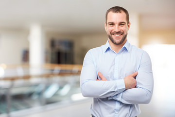 Smiling businessman stands in the business center with crossed arms