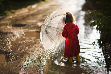 Happy child  with an umbrella playing out in the rain in the summer outdoors Wall mural