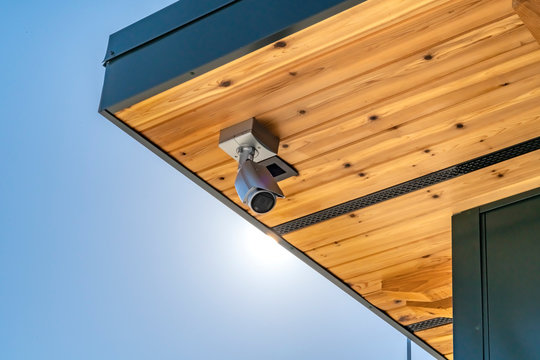 Home with security camera installed on the wooden underside of its roof