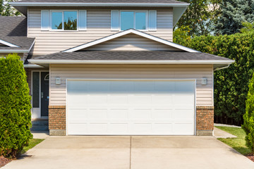 Wide garage door of residential house with concrete driveway in front