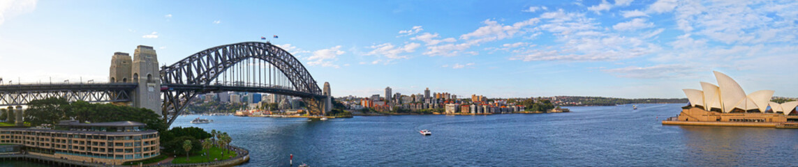 Panoramic view of Sydney harbor bridge and North Sydney, boats sailing in the bay and Parramatta River. Evening Light