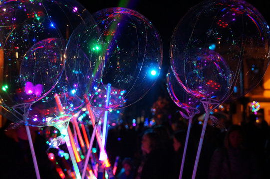 Festivities at night. A stand selling luminous toys: balloons and swords