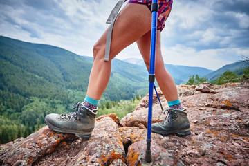 a young woman standing on the edge of a cliff after hiking up a mountain in Colorado