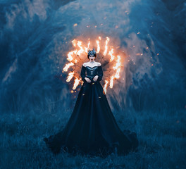 dark queen of night, majestic priestess in long black dress with bare shoulders, witch raven in a burning spider web, powerful devil with metal cold crown on her head, mistress and fire goddess
