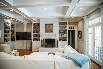 Large Living Room Den in Home with Vaulted Tray Ceiling and bookshelves