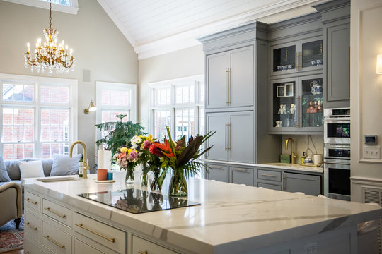 Open Concept Elegant and Spacious Kitchen with Marble Countertops, Chandelier, and Two Toned Cabinets