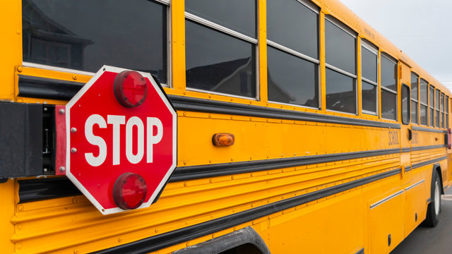 Panorama Exterior view of a yellow school bus with a red stop sign and signal lights
