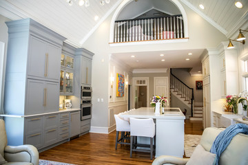 View of Upper Loft of Open Concept Home with eat in kitchen and Wood railing and Can Lighting