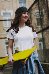Happy hipster girl walking with yellow skateboard