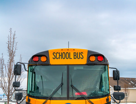Front view of a yellow school bus with homes and cloudy sky in the background