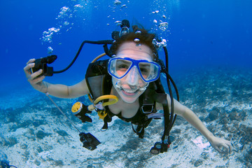 Female scuba diver smiling underwater - female scuba diver, using a blue mask, holding the regulator on one hand and smiling to the camera on a deep blue ocean, in Mexico (Cozumel island).