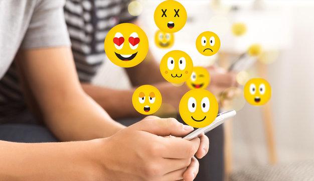 Social concept. Teen guy using smartphone sending emojis