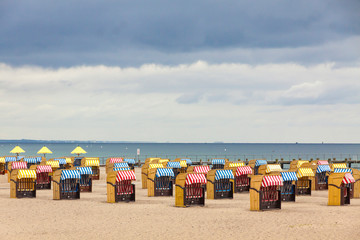 Colorful striped wooden hooded beach chairs (strandkorb) on a sandy Baltic beach in...
