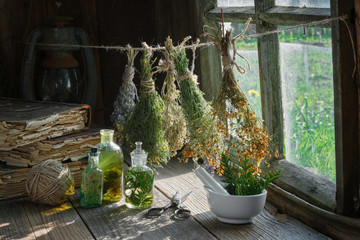 Tincture or infusion bottles, old books, mortar and hanging bunches of dry medicinal herbs. Herbal medicine. Fototapete