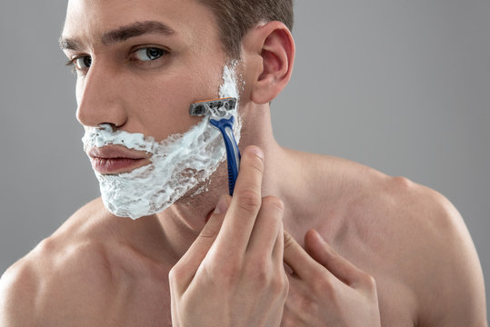 Handsome young man shaving with disposable razor