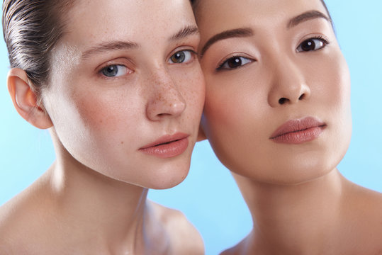 Close up of two interracial attractive women situating against blue background