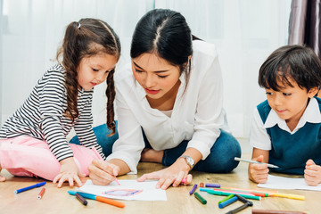 Family happy child kid girl kindergarten paint drawing on peper teacher education with mother mom