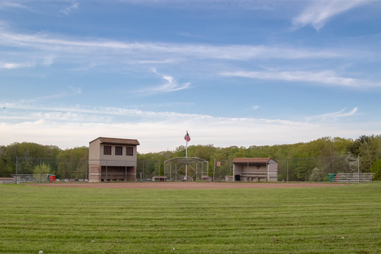 Baseball field from an outfield prospective, American flag flying between the dugouts.