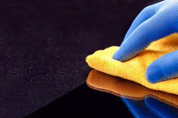 Hand in protective glove wiping dust layers on the furniture  with yellow dry rag. General or regular cleanup. Commercial cleaning company. Copy space.