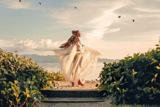 beautiful young fashion model having fun spinning around at sunset