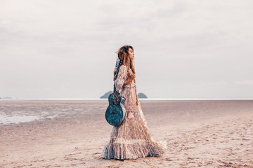 beautiful young fashion model in white dress with guitar outdoors at sunset