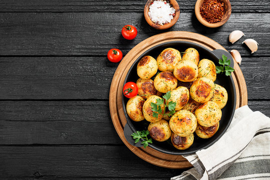 Roasted new potato in frying pan on black wooden background.