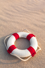 Retro Life Preserver at Holiday Sand Beach / Nostalgic miniature life buoy with rope and red stripes on wavy beach sand background (copy space)