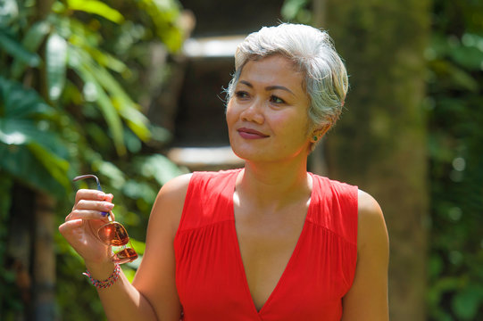 natural lifestyle portrait of beautiful and happy middle aged 40s or 50s Asian woman with grey hair in stylish red dress walking on green tropical jungle landscape