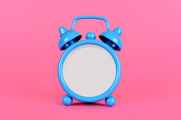 Blue classic alarm clock without hands and numbers on pink background.