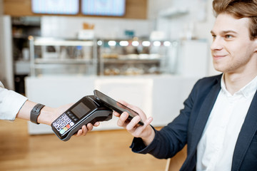 Young businessman paying contactless with smart phone while sitting at the cafe
