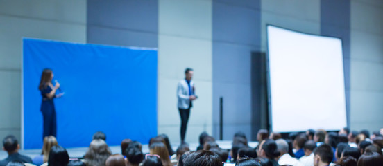 Audience watch blurred speakers giving speech in conference. Presenters in backgound at meeting during public speech. Defocused businessman in seminar with bokeh. People at corporate training event.