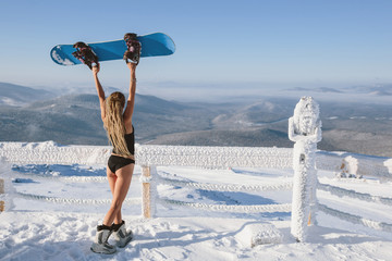 Woman wearing bikini and t-shirt with snowboard standing on snow mountain top in ski resort. Beautiful mountains view background, frozen sunny morning, frost on the binocular