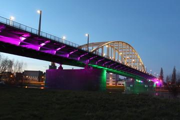 John Frost Bridge in Arnhem during blue hour while colorful lights shine on the bridge