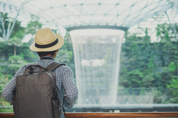 young man with bag and hat, Asian traveler standing and looking to beautiful rain vortex at Jewel Changi Airport, landmark and popular for tourist attractions in Singapore. Travel concept Fototapete