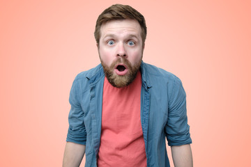 Surprised, emotional bearded man opened his mouth wide with amazement. Isolated on a coral background.