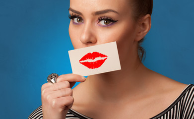 Person smiling with a card on the front of his mouth with a red lips on it