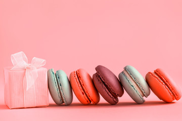 Pink present and Row of french colorful macaroons , lying on coral background.