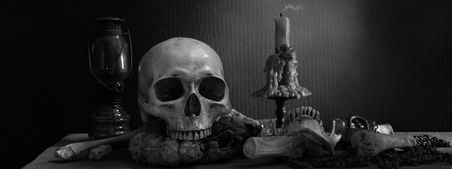 Skull on rotten pumpkin with candle light and lantern on the plank and  pile of bones