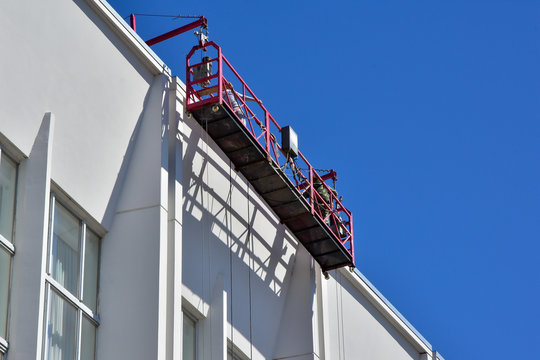 Specially equipped cradle on the facade of the building. Moves vertically along the facade to perform repairs and clean the building.