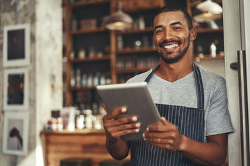 Smiling male cafe owner holding digital tablet in his hand
