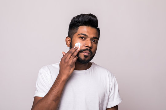 Portrait of satisfied young indian man applying facial cream isolated over white background